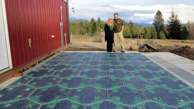 In this May 2014, photo provided by Solar Roadways, Scott and Julie Brusaw stand for a photo on a prototype solar-panel parking area at their company's business in Sandpoint, Idaho. Scott Brusaw's idea for solar-powered roads has gone viral and raised more than $1.4 million in crowdsourced funding. Brusaw is proposing to pave driveways, parking lots, bike trails and, eventually, highways with hexagon-shaped solar panels that will produce electricity and could even propel electric cars. (AP Photo/Solar Roadways)