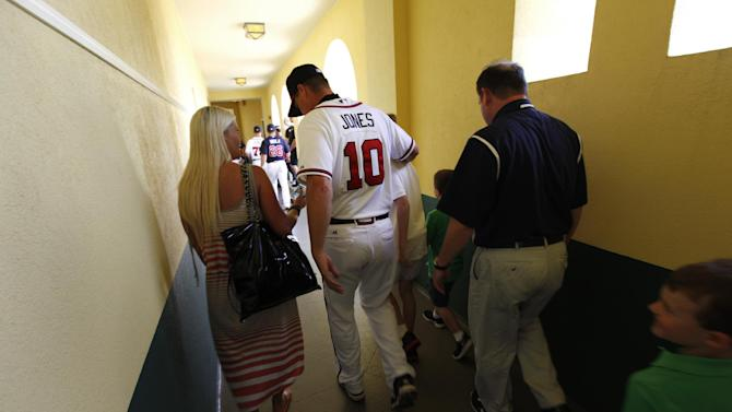 Atlanta Braves third baseman Chipper Jones (10) leaves a news conference with his family after announcing that he will retire following the 2012 season, before a spring training baseball game against the Miami Marlins in Kissimmee, Fla., Thursday, March 22, 2012.  (AP Photo/Paul Sancya)