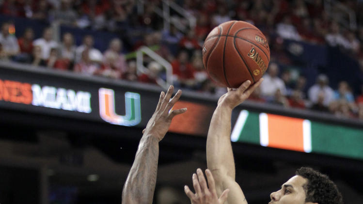Miami's Shane Larkin, right, shoots over North Carolina State's Richard Howell, left, during the first half of an NCAA college basketball game in the semifinals of the Atlantic Coast Conference tournament in Greensboro, N.C., Saturday, March 16, 2013. (AP Photo/Bob Leverone)