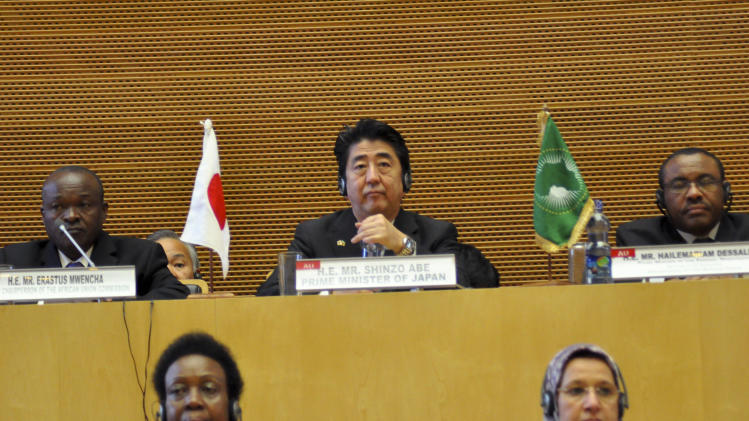 Japan's Prime Minister Shinzo Abe, center, sits between Ethiopia's Prime Minister Hailemariam Desalegn, right, and Deputy Chairperson of the African Union Commission Erastus Mwencha, left, during Abe's visit to the African Union (AU) headquarters in Addis Ababa, Ethiopia Tuesday, Jan. 14, 2014. The visit comes at the end of Abe's weeklong African tour designed to restore Japan's global influence in the face of China's rise, as well as help Japanese companies win business overseas. (AP Photo/Elias Asmare)