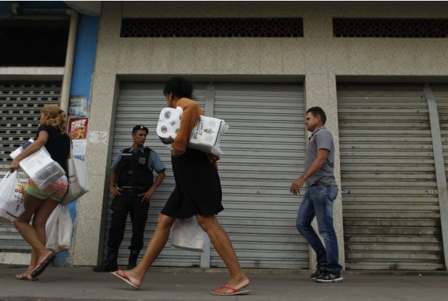A police officer stands guard as people walk past closed shops at the Complexo do Alemao slum in Rio de Janeiro