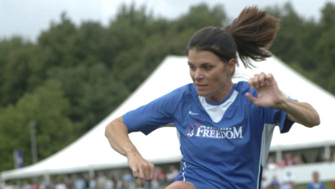 "FILE -- In this file photo taken on Aug. 26, 2007, Mia Hamm, playing for the Washington Freedom, takes a pass while playing against the SoccerPlus Connecticut Reds during the Hall of Fame Game at the National Soccer Hall of Fame in Oneonta, N.Y. With three kids at home, Mia Hamm already had plenty on her plate when two professional clubs came calling over the space of a few days in October. They weren't asking her to play _ the 42-year-old soccer star has been retired for more than a decade _ rather they wanted her to join their management sides. It all kind of happened in one week,"" Hamm told The Associated Press during an interview on Monday March 2, 2015. ""It was kind of crazy."" Hamm and her husband, ex-baseball star Nomar Garciaparra, joined an ownership group for LAFC, while Hamm alone was asked by Pallotta to join Roma's board of directors in a purely advisorial role.  (AP Photo/Hans Pennink, file)"