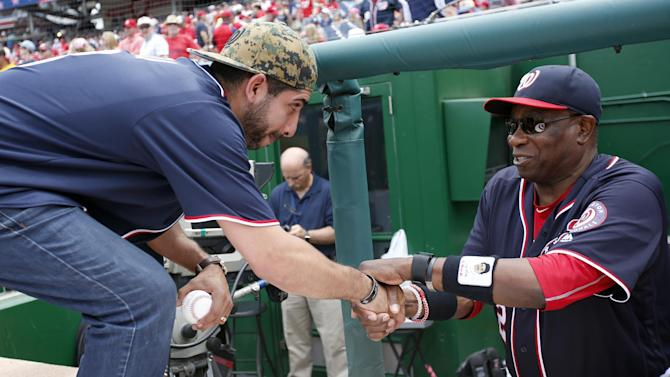 """Medal of Honor recipient retired U.S. Army Capt. Florent """"Flo"""" Groberg, left, is greeted by Washington Nationals manager Dusty Baker before a baseball game between the Nationals and the St. Louis Cardinals at Nationals Park, Sunday, May 29, 2016, in Washington. (AP Photo/Alex Brandon)"""