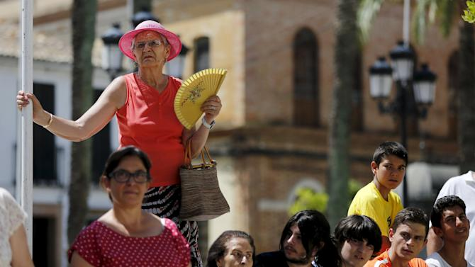People wait for Spain's Prime Minister Rajoy visit to the town of La Palma del Condado, southern Spain