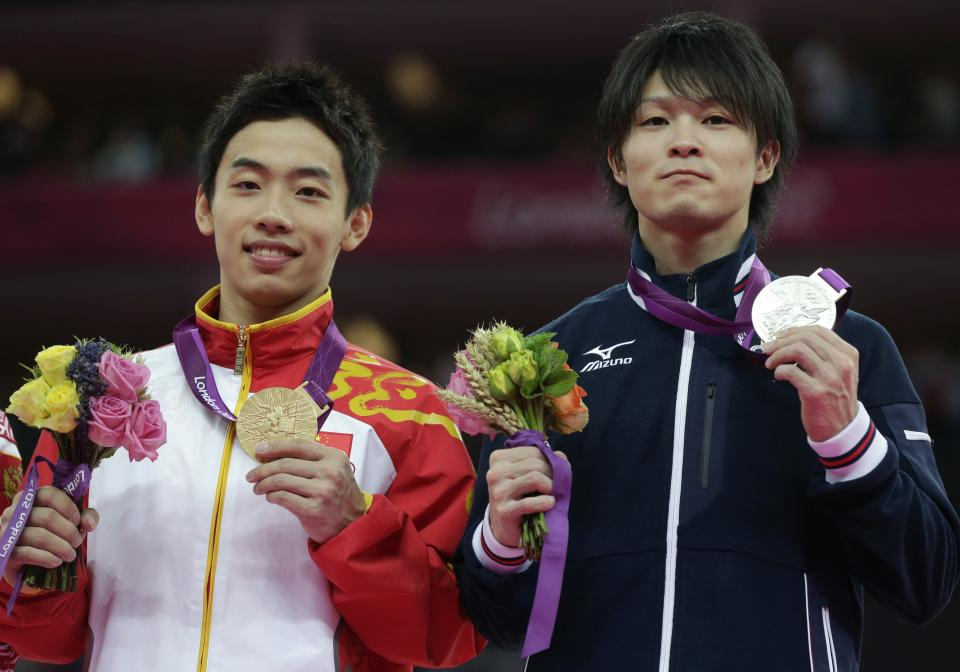 Chinese gymnast Zou Kai, left, and Japanese gymnast Kohei Uchimura display their gold and silver medals during the podium ceremony for the men's floor exercise finals at the 2012 Summer Olympics, Sunday, Aug. 5, 2012, in London. (AP Photo/Julie Jacobson)