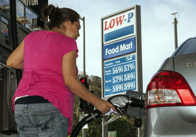 Motorist Elisabeth Chavarria fills up only six dollars worth of gas to be able to drive home Friday, Oct. 5, 2012, at the Low-P, an independent gas station in Calabasas, Calif. Californians woke up to a shock Friday as overnight gasoline prices jumped by as much as 20 cents a gallon in some areas, ending a week of soaring costs that saw some stations close and others charge record prices. (AP Photo/Damian Dovarganes)
