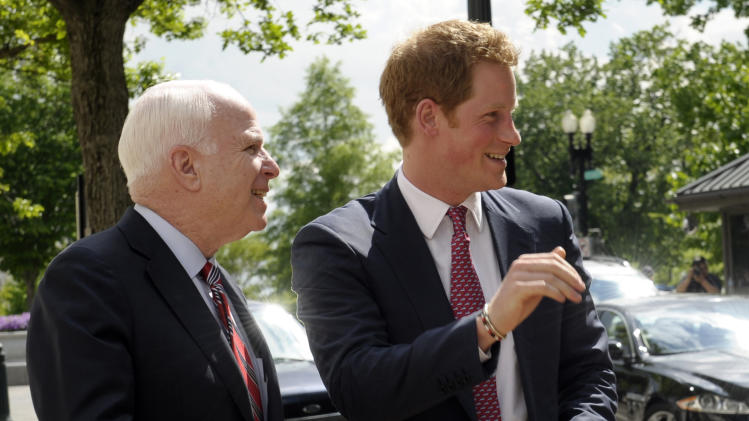Prince Harry, right, and Sen. John McCain, R-Ariz., left, look over at the crowd watching after Prince Harry arrived on Capitol Hill, Washington, Thursday, May 9, 2013, to view an exhibition staged by the HALO Trust. (AP Photo/Susan Walsh)