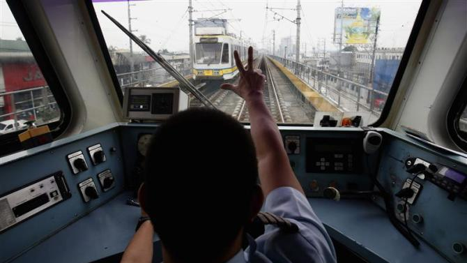 A train operator on Southeast Asia's first light rail transit network signals to a colleague in another train in Manila