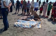 In this photo taken with a mobile phone, villagers stand around the bodies of the victims of a boat that sank off Java island, on Sinarlaut beach in Agrabinta, West Java, Indonesia, Friday, Sept. 27, 2013.The boat carrying dozens of asylum seekers sank en route to Australia off the coast of Indonesia's main island of Java on Friday, an official said. (AP Photo)