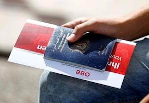 A migrant holds his passport and a train ticket in …