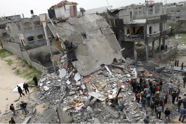 Palestinians inspect the rubble of a destroyed building following an Israeli air strike in Jabaliya, Monday, March 12, 2012. Israeli air strikes killed two Palestinian militants and a schoolboy in the