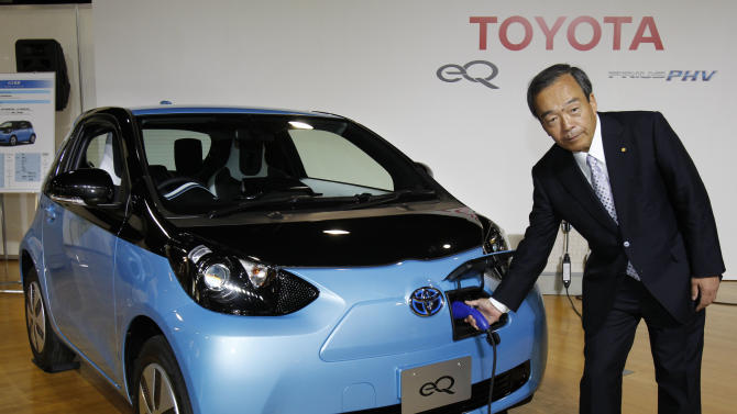 """Toyota Motor Corp. Vice Chairman Takeshi Uchiyamada puts a plug to the newly-developed compact electric vehicle """"eQ"""" during a  press conference in Tokyo, Monday, Sept. 24, 2012. Toyota is boosting its green vehicle lineup, with plans for 21 new hybrids in the next three years, a new electric car later this year and a fuel cell vehicle by 2015 in response to growing demand for fuel efficient and environmentally friendly driving. (AP Photo/Koji Sasahara)"""