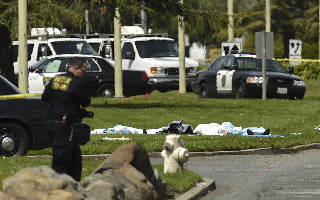 Bodies lie covered on the grass as Oakland Police work near Oikos University in Oakland, Calif., Monday, April 2, 2012. A gunman opened fire at Oikos University in California Monday, killing at least five people, law enforcement sources close to the investigation said. Police say they have a suspect in custody. (AP Photo/Noah Berger)