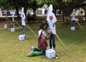 A student writes a message on a cut-out figure of an active rebel of the FARC during an event to campaign for FARC demobilisation in Tame