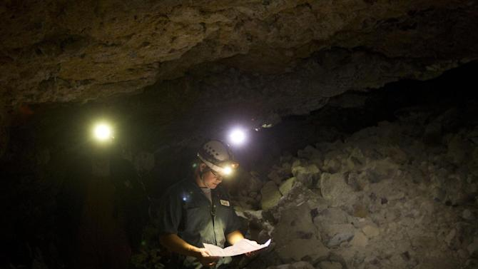In this photo taken, Friday, May 15, 2015, Jeremy Callen reviews where the group is during an expedition at Gypsum Cave near Shoshone, Idaho. One section of the cave has six traversable layers of tube, separated by rock. Pieces of the dividing rock collapsed, leaving huge rooms with multiple stories ,  and precarious sidewalks clinging to the walls. (Drew Nash/The Times-News via AP) MANDATORY CREDIT