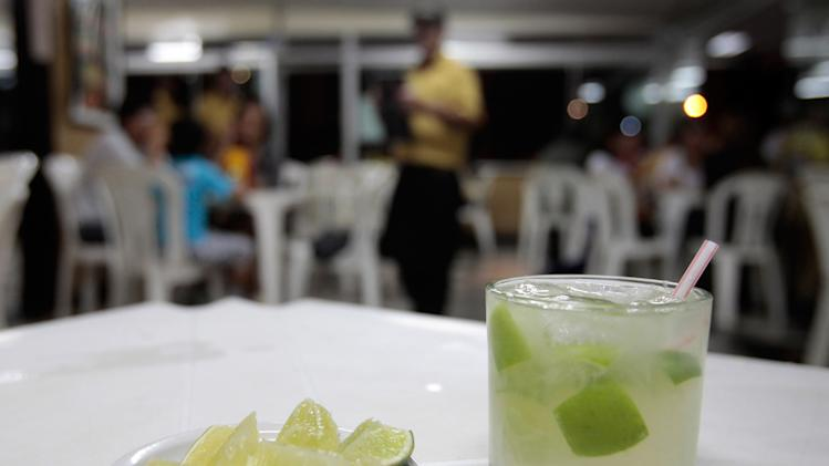 "In this April 11, 2013 photo, a glass of ""caipirinha"" sits on a restaurant table in Brasilia, Brazil, April 11, 2013. The vast majority of cachaca, Brazil's national spirit, is consumed domestically, much of it sipped in Brazil's famed caipirinha cocktails with lime, sugar and crushed ice. (AP Photo/Eraldo Peres)"