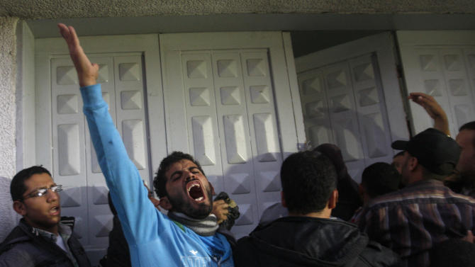 Palestinian men react at hospital after the body of Ahmed Jabari, head of the Hamas military wing, was brought,  in Gaza City, Wednesday, Nov. 14, 2012. The Israeli military said its assassination of the Hamas military commander marks the beginning of an operation against Gaza militants. (AP Photo/Hatem Moussa)