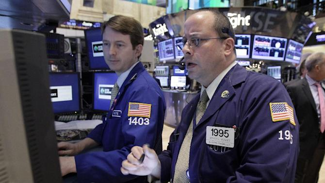 FILE - In this  Tuesday, Dec. 11, 2012 file photo, trader Jeffrey Vazquez, right, works on the floor of the New York Stock Exchange. Any enthusiasm over another monetary stimulus from the Federal Reserve faded Thursday Dec. 13, 2012 as investors monitored the progress of budget discussions in the U.S. (AP Photo/Richard Drew, File)