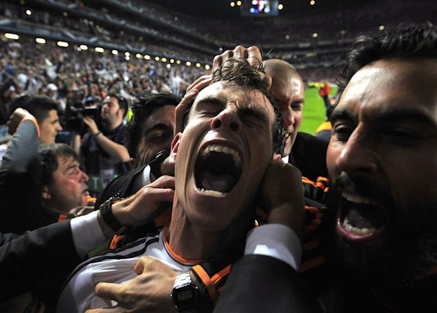 Real Madrid's Gareth Bale celebrates with teammates after scoring his side's second goal in the Champions League final soccer match against Atletico Madrid at the Luz Stadium in Lisbon, Portugal, Saturday, May 24, 2014. Real Madrid won 4-1 in extra time. (AP Photo/Manu Fernandez)