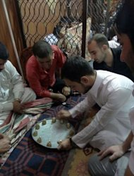 "Turkman, Arab and Kurdish residents of Kirkuk play the ""Siniyah,"" or tray game, in the northern multi-ethnic city on August 4, a tradition during the long evenings of the holy fasting month of Ramadan. Siniyah remains one of the few apolitical traditions in the disputed city of northern Iraq"