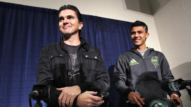"""Latin musician Juanes, left, and Seattle Sounders FC forward Fredy Montero smiles following a news conference about Juanes upcoming tour Tuesday, March 8, 2011, in Seattle. Juanes kicks-off his world """"P.A.R.C.E. Tour"""" Thursday March 10, in Seattle. (AP Photo/Elaine Thompson)"""