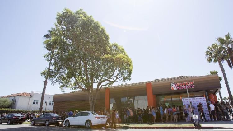People stand in line outside a newly opened Dunkin' Donuts store in Santa Monica