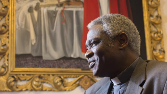 ADD FEB. 12 - Ghanaian Cardinal Peter Kodwo Appiah Turkson talks to the Associated Press during an interview, in Rome, Tuesday, Feb. 12, 2013. One of Africa's brightest hopes to be the next pope, Ghanaian Cardinal Turkson, says the time is right for a pontiff from the developing world. In the background is a painting of late Pope John Paul II.  (AP Photo/Domenico Stinellis)