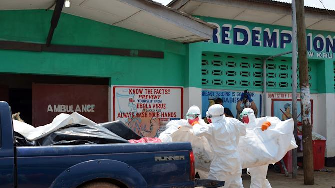 Liberian health workers wear protective suits as they remove the body of an Ebola victim from a clinic in Monrovia, on September 12, 2014