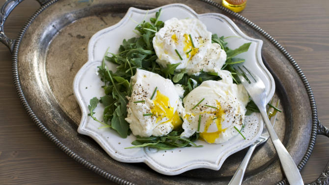 In this image taken Dec. 3, 2012, poached eggs over ricotta cheese on arugula are shown served on a plate in Concord, N.H. (AP Photo/Matthew Mead)