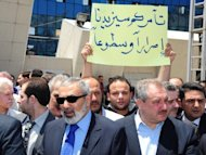 "Picture from the official Syrian news agency SANA shows a demonstrator holding a sign which reads, ""Your conspiracy will only make us more determined and bright"" outside the pro-government Al-Ikhbariya satellite television channel's offices outside Damascus on June 27. Kofi Annan is proposing a transitional government for Syria including members from both sides, diplomats said"