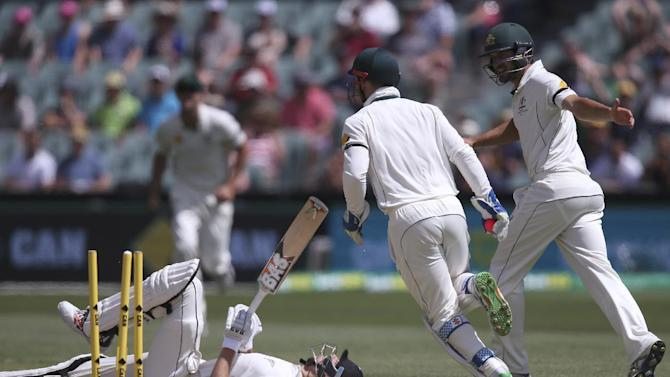 New Zealand's Mitchell Santner, left, lays on the ground after he was stumped by Australia's Peter Nevill, second from right, during their cricket test in Adelaide, Australia, Sunday, Nov. 29, 2015. This match is the sport's first ever day-night test. (AP Photo/Rick Rycroft)
