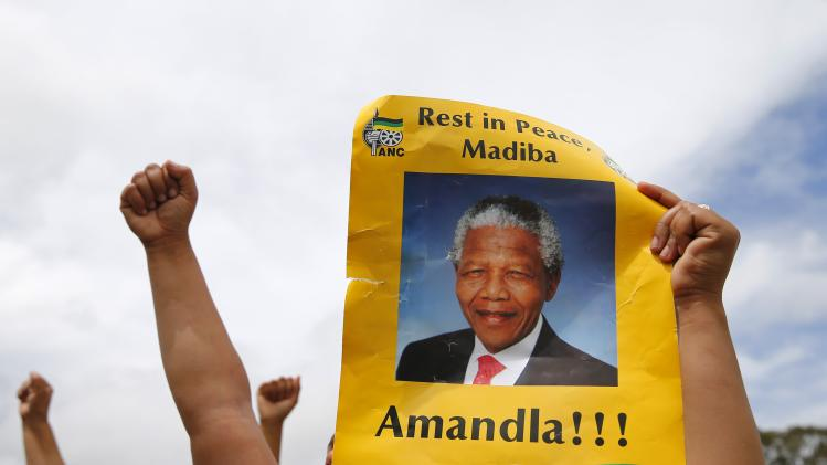 A woman holds up a poster of former South African President Nelson Mandela given out by African National Congress (ANC) members just outside the village of Qunu