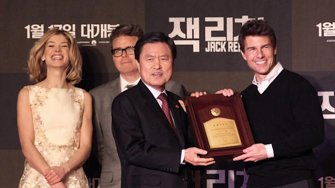 "U.S. actor Tom Cruise, right, receives a certificate of Busan citizenship from Busan City mayor Hut Nam-shik, second from right, before a premiere of his new movie ""Jack Reacher"" as British actress Rosamund Pike, left, and director Christopher McQuarrie look on at the Busan Cinema Center in Busan, South Korea, Thursday, Jan. 10, 2013. (AP Photo/Ahn Young-joon)"