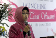 "In this Saturday, June 18, 2011 photo, Gina Puspita, the leader of ""Klub Taat Suami,"" or ""Obedient to Husband Club,"" delivers her speech during the launching ceremony of the newly-formed group at a restaurant In Jakarta, Indonesia. The new club that aims to encourage women to be pious and totally obedient to their husbands has generated an outcry from some activists. Writings on the background say ""Launching, Obedient to Husband Club."" (AP Photo/Dita Alangkara)"