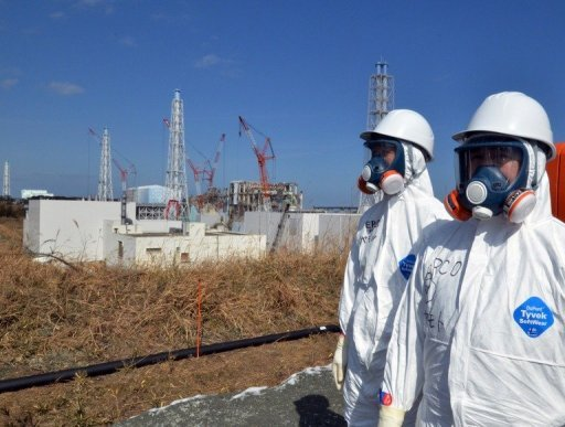 Tokyo Electric Power Co (TEPCO) workers stand before the stricken Fukushima nuclear plant