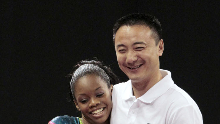 Gabby Douglas, left, is congratulated by her coach, Liang Chow, after competing in the vault at the U.S. gymnastics championships Sunday, June 10, 2012, in St. Louis. Douglas finished in second place overall. (AP Photo/Jeff Roberson)