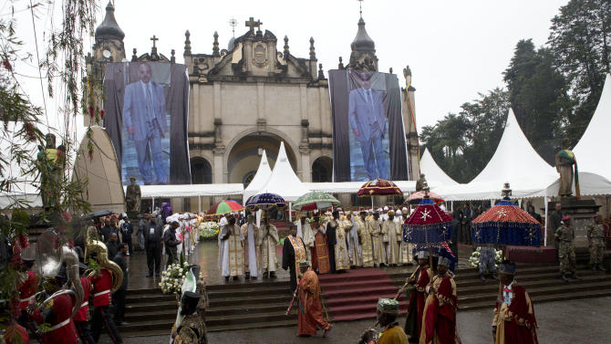 A marching band and Ethiopian clerics lead the procession as the body of late Prime Minister Meles Zenawi arrives at Holy Trinity Cathedral for burial, in Addis Ababa, Ethiopia, Sunday, Sept. 2, 2012. Thousands of mourners gathered in a public square in Ethiopia's capital on Sunday to pay their final respects to Zenawi, who was praised for lifting many out of poverty but vilified by some for restricting freedoms. Zenawi, who ruled for 21 years, died Aug. 20 of an undisclosed illness in a Belgian hospital. He was 57. (AP Photo/Rebecca Blackwell)