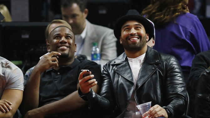 Major League Baseball player Matt Kemp, far right, of the San Diego Padres smiles as the crowd reacts to him being shown on the scoreboard screen during the first half of an NBA basketball game between the Los Angeles Clippers and Milwaukee Bucks Saturday, Dec. 20, 2014, in Los Angeles. (AP Photo/Danny Moloshok)