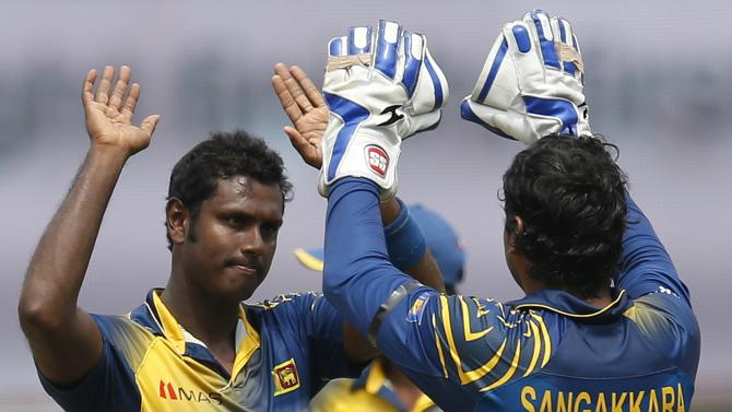 Sri Lanka's captain Mathews celebrates with teammate Sangakkara after taking the wicket of England's Root during their second ODI cricket match in Colombo