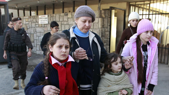 Russian family walk together shortly after crossing the border from Syria into Lebanon at the Masnaa border crossing in eastern Lebanon, Tuesday, Jan. 22, 2013. Some 80 Russian citizens crossed into Lebanon as Moscow began evacuating some of the tens of thousands of Russians who live in Syria. (AP Photo/Bilal Hussein)