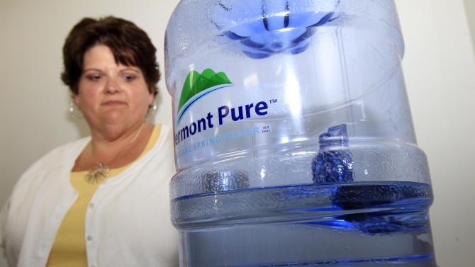 In this July 22, 2011 photo, Lori Girard-Pion stands by the water cooler at her state office in Colchester, Vt. Vermont state officials, who announced in March that they would pull the plug on water coolers and bottled water deliveries in state offices and buildings, are reconsidering the move amid a wave of complaints from workers. Calling bottled water a waste of taxpayer money, the state had said it hoped to save up to $200,000 annually by having workers use fountains and tap water instead. They said the change would help the environment, too, since toxic chemicals go into the making of plastic water bottles and ecologically-sensitive stream headwaters areas are damaged in the process of bottling. But many state workers have since complained that the tap water in their buildings is dirty or that they'll have no way to get clean drinking water if the state stops buying bottled water for them. (AP Photo/Toby Talbot)