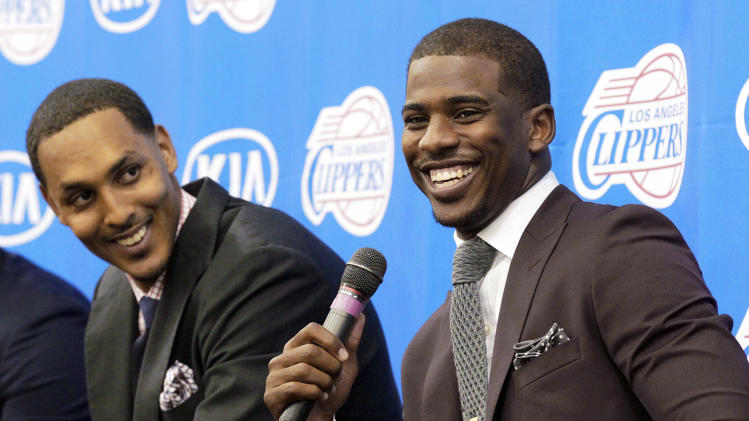 Los Angeles Clippers players Chris Paul, right, and Ryan Hollins talk to reporters as the Clippers announce updates and additions to their NBA basketball team roster at their headquarters in Los Angeles, Wednesday, July 10, 2013. (AP Photo/Reed Saxon)