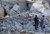 Boys walk amidst the rubble of damaged buildings in Duma neighbourhood of Damascus September 23, 2013. REUTERS/Bassam Khabieh