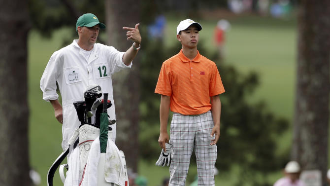 Amateur Guan Tianlang, of China, discusses his shot with caddie Brian Tam on the first fairway during the second round of the Masters golf tournament Friday, April 12, 2013, in Augusta, Ga. (AP Photo/Darron Cummings)