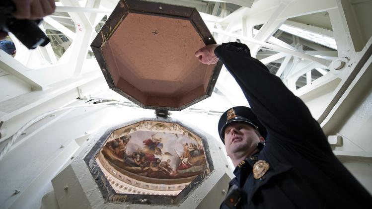 U.S. Capitol Police Officer Taylor holds open a coffer window in the ceiling of the U.S. Capitol dome during media tour in Washington