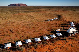 A string of 15 tents dotting a sand dune in the Outback.
