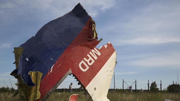 A man walks past a piece of the crashed Malaysia Airlines Flight 17 near the village of Hrabove, eastern Ukraine Monday, July 21, 2014. Four days after Flight 17 was shot out of the sky, international investigators still have had only limited access to the crash site, hindered by pro-Russia fighters who control the verdant territory in eastern Ukraine. Outrage over the delays and the possible tampering of evidence at the site was building worldwide, especially in the Netherlands, where most of the victims were from. (AP Photo/Dmitry Lovetsky)