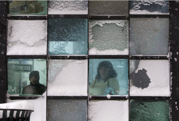 Riders wait in a bus stop where color-tinted windows collect snow during a storm, Friday, Feb. 8, 2013, in Portland, Maine. The National Weather Service says a blizzard warning is issued Friday evenin