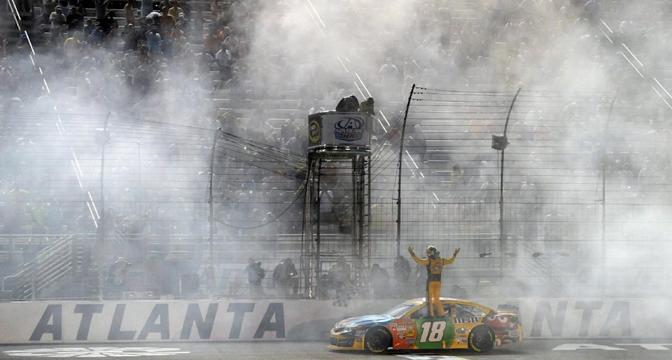 Sprint Cup Series driver Kyle Busch (18) celebrates after winning the NASCAR Sprint Cup Series auto race at Atlanta Motor Speedway in Hampton, Ga., Sunday, Sept. 1, 2013. (AP Photo/David Tullis)