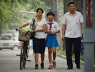 A family make their way along a street in Beijing. China&#39;s one-child policy normally leaves four grandparents and two parents relying on a single caretaker for old age -- and bereaved families with none